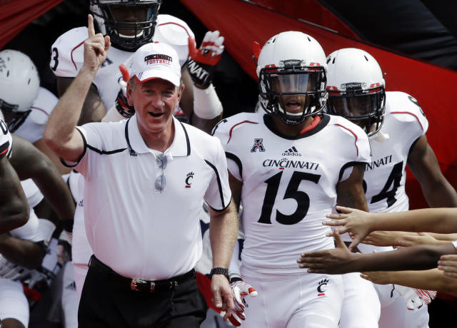 Cincinnati head coach Tommy Tuberville, left, leads his team onto the field at the start of an NCAA college football game against Purdue, Saturday, Aug. 31, 2013, in Cincinnati. Tuberville was coaching his first game for Cincinnati. (AP Photo/Al Behrman)