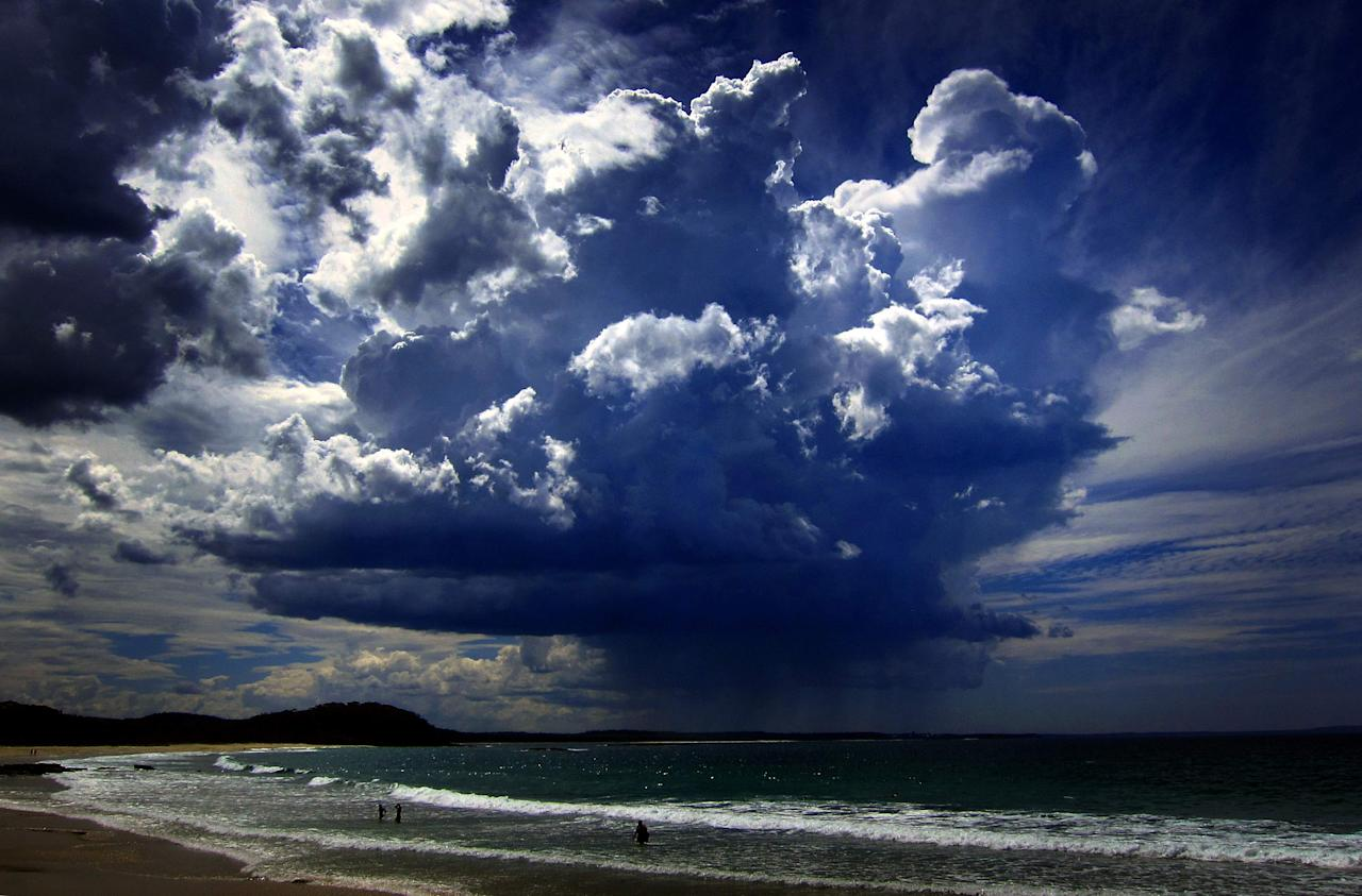 A giant storm cloud can be seen in the sky above swimmers near Mollymook Beach, south of Sydney March 5, 2014. The storm generated heavy rain and high gusts of wind. REUTERS/David Gray (AUSTRALIA - Tags: ENVIRONMENT TPX IMAGES OF THE DAY)