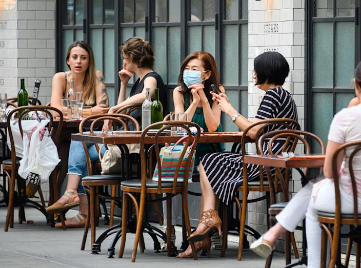 NEW YORK, NEW YORK - JUNE 30: People sit outside The Smith on the Upper East Side as New York City moves into Phase 2 of re-opening following restrictions imposed to curb the coronavirus pandemic on June 30, 2020. Phase 2 permits the reopening of offices, in-store retail, outdoor dining, barbers and beauty parlors and numerous other businesses. Phase 2 is the second of four phased stages designated by the state. (Photo by Noam Galai/Getty Images)