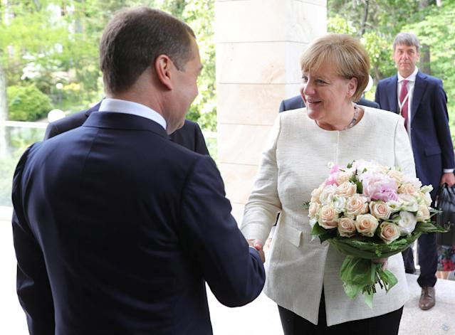 Russian Prime Minister Dmitry Medvedev welcomes German Chancellor Angela Merkel during their meeting in the Black Sea resort of Sochi, Russia May 18, 2018. Sputnik/Mikhail Klimentyev/Kremlin via REUTERS ATTENTION EDITORS - THIS IMAGE WAS PROVIDED BY A THIRD PARTY.