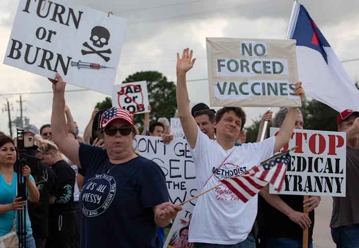 Protesters wave signs at Houston Methodist Baytown Hospital in Baytown, Texas, on Monday, June 7, 2021.