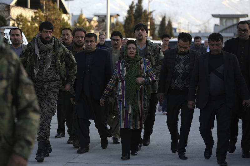 Hawa Alam Nuristani, center, chief of the Election Commission of Afghanistan, center, arrives for a press conference at the Independent Election Commission office in Kabul, Afghanistan, Tuesday, Feb. 18, 2020. The Afghan Independent Election Commission said Tuesday that President Ashraf Ghani has won a second term as president. (AP Photo/Rahmat Gul)