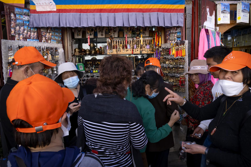 Members of a Chinese tour group shop at a souvenir shop outside of the Jokhang Temple in Lhasa in western China's Tibet Autonomous Region, Tuesday, June 1, 2021. Tourism is booming in Tibet as more Chinese travel in-country because of the coronavirus pandemic, posing risks to the region's fragile environment and historic sites. (AP Photo/Mark Schiefelbein)