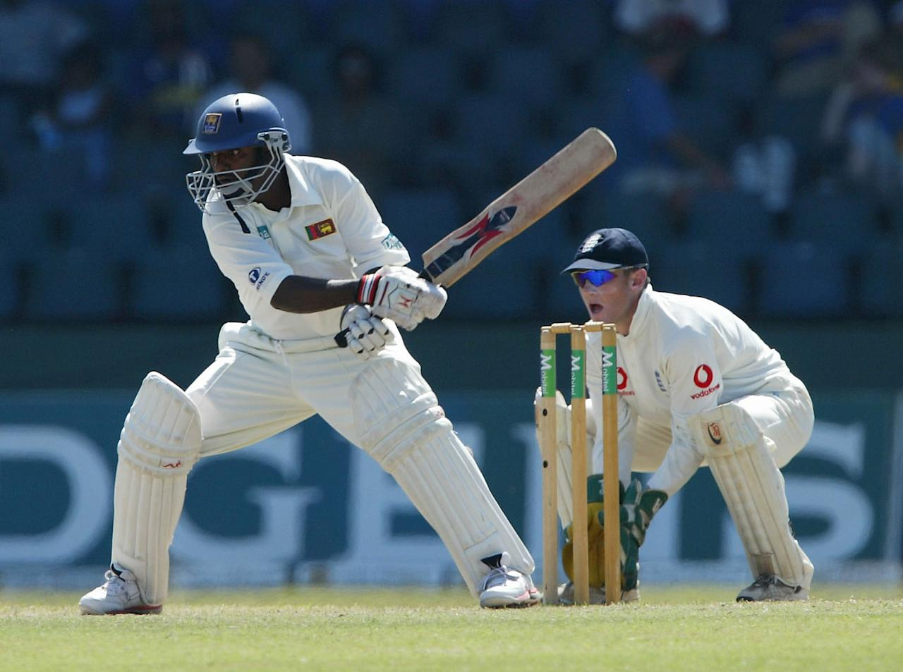 COLOMBO, SRI LANKA - DECEMBER 21:  Sri Lankan batsman Muttiah Muralitharan plays a reverse sweep watched by England wicketkeeper Chris Read during the fourth day of the third test between Sri Lanka and England today at The Singhalase Sports Club on December 21, 2003 in Colombo, Sri Lanka. Sri lanka won the match by a record innings and 215 runs to win the series 1-0. (Photo by Stu Forster/Getty Images).