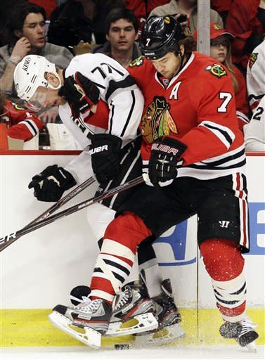 Los Angeles Kings' Jeff Carter (77) and Chicago Blackhawks' Brent Seabrook (7) battle for the puck during the first period of an NHL hockey game in Chicago, Sunday, March 11, 2012. (AP Photo/Nam Y. Huh)
