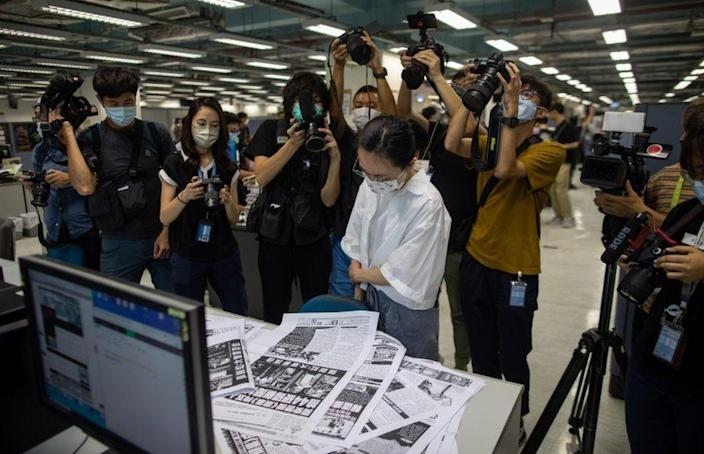 A proof reader surrounded by members of the media works in the newsroom of the Apple Daily newspaper on 17 June 2021