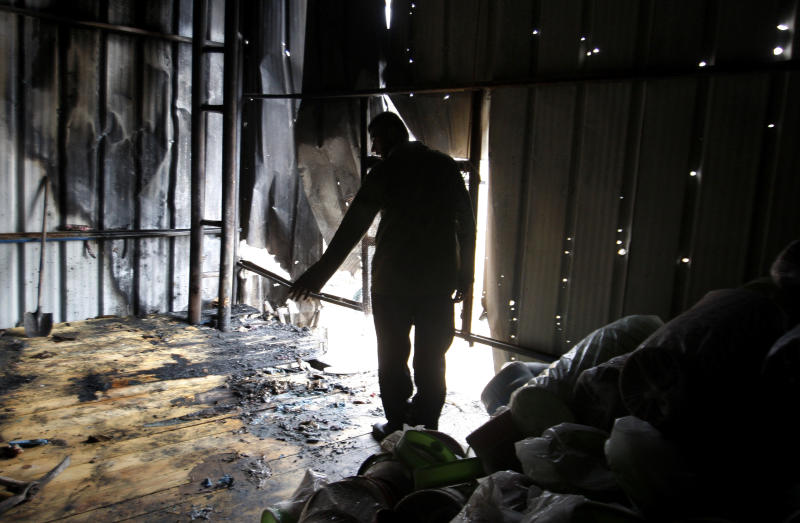 A Palestinian stands in a factory hit by an Israeli tank shell in Beit Hanoun, northern Gaza Strip, Sunday, Nov. 11, 2012. Hostilities along the Gaza-Israel border escalated sharply over the weekend, with bombardments from Gaza causing rare Israeli casualties and Israeli strikes killing at least six Palestinians. (AP Photo/Hatem Moussa)
