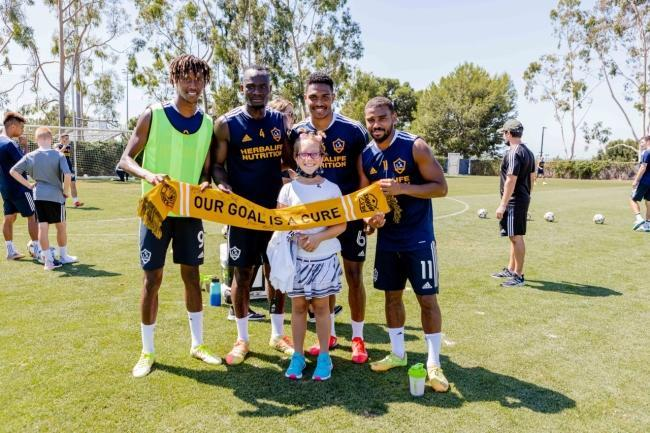 10-year-old Avery (center) meets with LA Galaxy players during practice at Dignity Health Sports Park during her Dream on 3 Sports Wish, in conjunction with MLS's Kick Childhood Cancer Campaign on September 15, 2021.