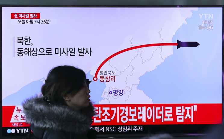 A visitor walks by a TV screen in Seoul showing a news report about a recent North Korean missile firing (Pictures: AP)