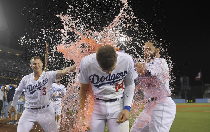Los Angeles Dodgers' Enrique Hernandez, center, is doused by Chris Taylor, left, and Russell Martin after driving in the winning run during the ninth inning of the team's baseball game against the Toronto Blue Jays on Thursday, Aug. 22, 2019, in Los Angeles. (AP Photo/Mark J. Terrill)