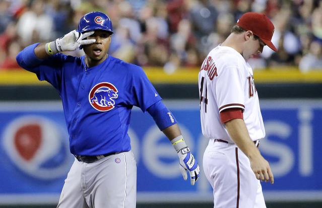 Chicago Cubs' Luis Valbuena, left, gestures to his bench after hitting a standup double during the fourth inning of a baseball game as Arizona Diamondbacks Paul Goldschmidt looks away, Friday, July 18, 2014, in Phoenix. (AP Photo/Matt York)