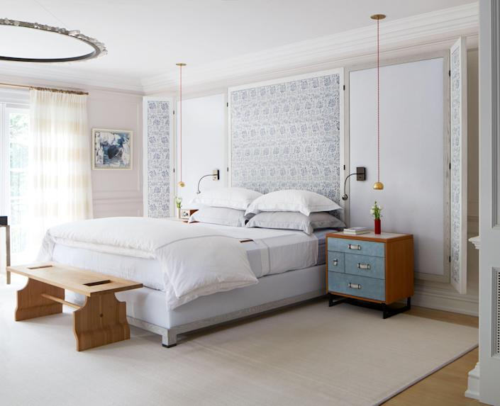 The platform bed in the primary bedroom features a Lona Design headboard upholstered in a Fortuny print. The circular rock-crystal-and-bronze pendant is by Christopher Boots; the bedside pendants with custom red cord are by Lindsey Adelman.