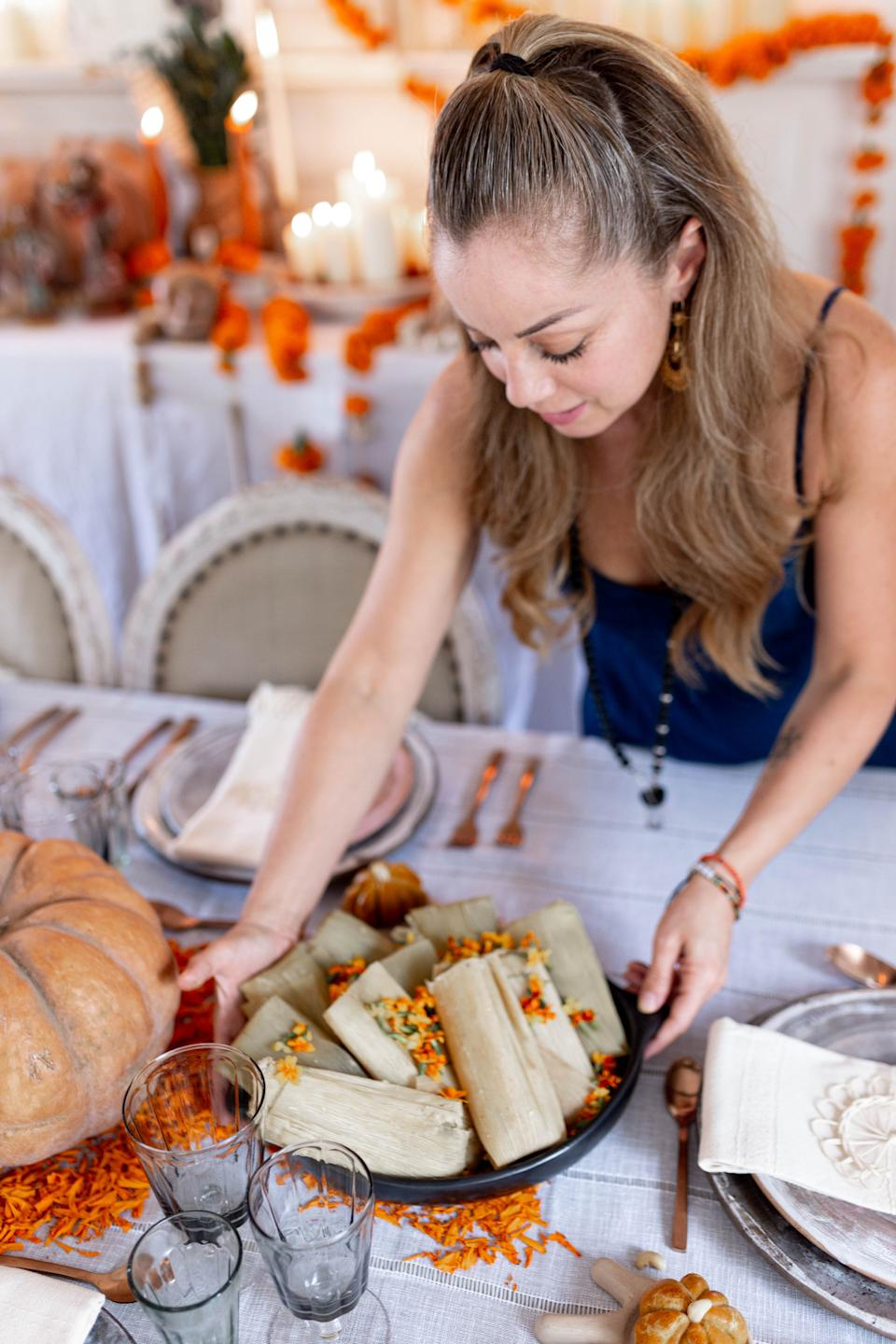 Valladolid places a plate of tamales on the table in front of her ofrenda. (Photo: Cecilia Martin Del Campo)