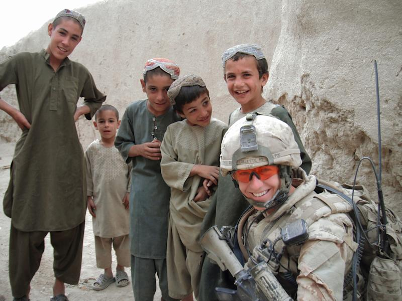 In this undated photo provided by Canadian Armed Forces Capt. Ashley Collette, she poses for a photo with children during a patrol in Afghanistan. During her 10-month deployment, Collette led a 50-strong all-male infantry unit providing security to villagers. Now 28, she received the Medal of Military Valour, Canada's third-highest military honor, for her leadership in the Panjwaii district near Kandahar. In 1989, a ruling by Canada's Human Rights Commission ordered women to be admitted to all combat roles except aboard submarines. The submarine ban fell three years later. (AP Photo/Capt. Ashley Collette)
