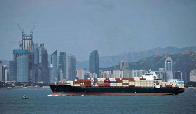 A container ship sails by the business district in Qingdao in east China's Shandong province. Photo: AP