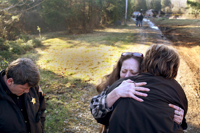 Crawford County, Ind., Sheriff Tim Wilkerson, left, and Deputy Debra Young, back to camera. comfort Rose Turben, center, as they stand in front of a mobile home where five of Turben's family members died in a mobile home fire Thursday, Feb. 7, 2013 in Sulpher, Ind.   Wilkerson said it took firefighters two hours to extinguish the fire that gutted the home, according to the The Courier Journal. (AP Photo/The Courier Journal, Aaron Borton)