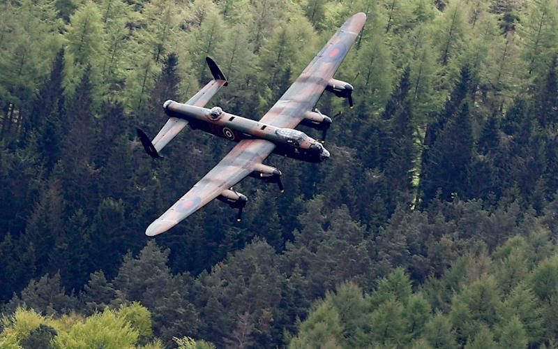 A Lancaster bomber swoops over Derwent Reservoir to mark the 70th anniversary of the raids - Credit: REUTERS/Darren Staples