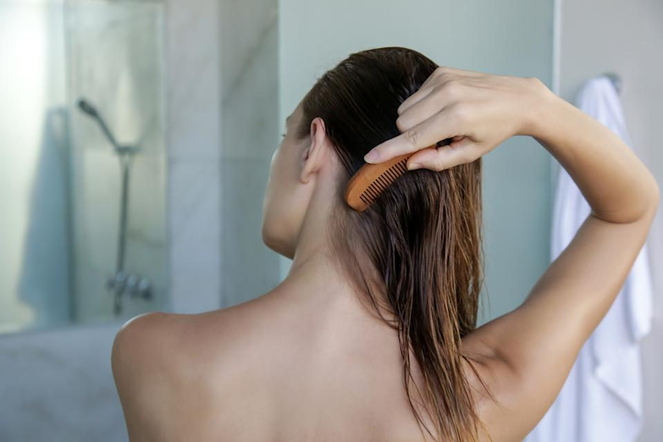 Hair care. Brunette woman combing damp hair with wooden comb.