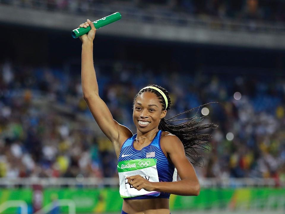 Allyson Felix holds up a baton at the Rio Olympics in 2016.