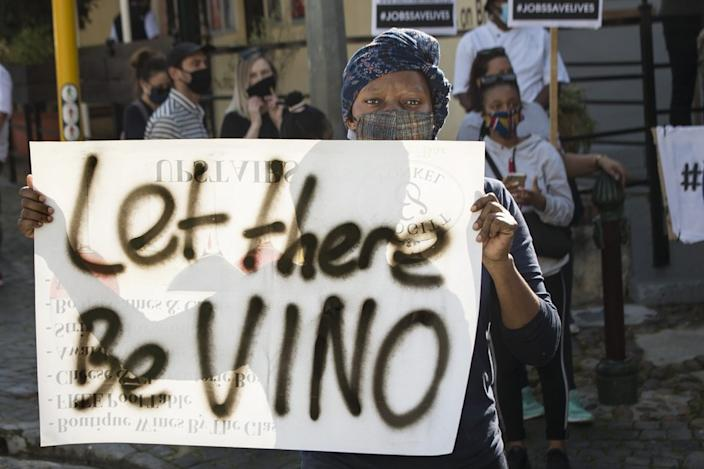 """Let there be VINO,"" reads this protester's sign in South Africa on Wednesday. Many in the hospitality industry say the ongoing lockdown places their jobs and businesses at risk."