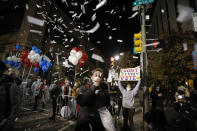 A demonstrator tosses confetti outside the Pennsylvania Convention Center where votes are being counted, Thursday, Nov. 5, 2020, in Philadelphia, following Tuesday's election. (AP Photo/Rebecca Blackwell)