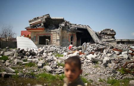 An Iraqi boy walks past a building destroyed during the fighting between Iraqi forces and Islamic states militants in Qayyara