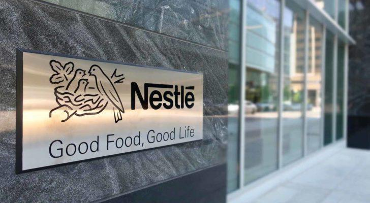 A close-up of the Nestle (NSRGY) logo near a corporate office entrance.