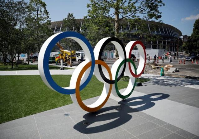 FILE PHOTO: Construction workers and passersby are seen through Olympic rings in front of the construction site of the New National Stadium, in Tokyo