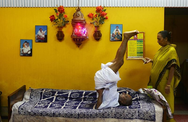 Indian monk Swami Sivananda (C), who claims to be 120 years old, is watched by one of his followers while practicing yoga in Kolkata on August 2, 2016 (AFP Photo/Dibyangshu Sarkar)