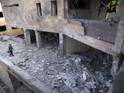 A journalist examines a newly built natal center damaged by shelling by Azerbaijan's artillery in Stepanakert, the separatist region of Nagorno-Karabakh, Wednesday, Oct. 28, 2020. Nagorno-Karabakh officials said Azerbaijani forces hit Stepanakert, the region's capital, and the nearby town of Shushi with the Smerch long-range multiple rocket systems, killing one civilian and wounding two more. (AP Photo)