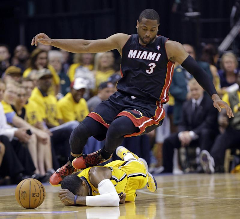 Miami Heat guard Dwyane Wade (3) goes over Indiana Pacers forward Paul George as they went for a loose ball during the fourth quarter of Game 2 of the NBA basketball Eastern Conference finals in Indianapolis, Tuesday, May 20, 2014. The Heat defeated the Pacers 87-83 to tie the series at 1-1