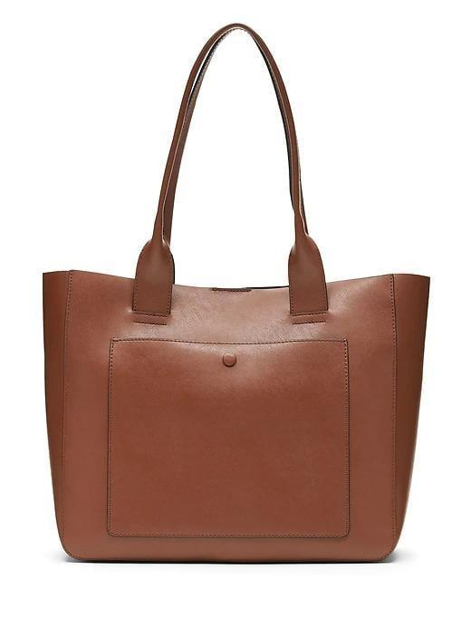 <p>Whether they got a new job, landed a promotion, or are the type to carry their entire life with them at all times, a <span>Leather East-West Tote</span> ($168) is a gift they'll love opening this year. </p>