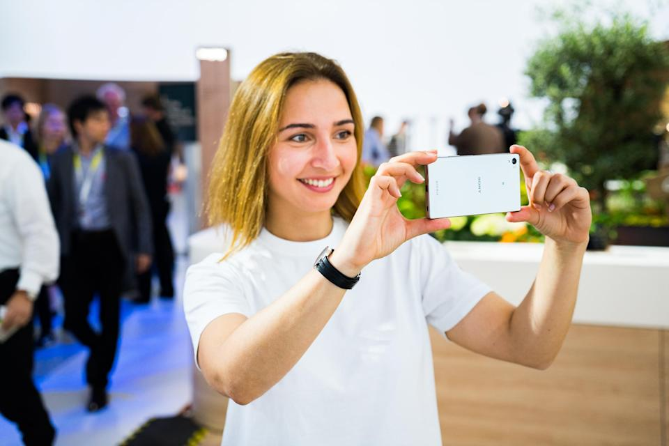 A woman takes a picture with an Xperia phone.