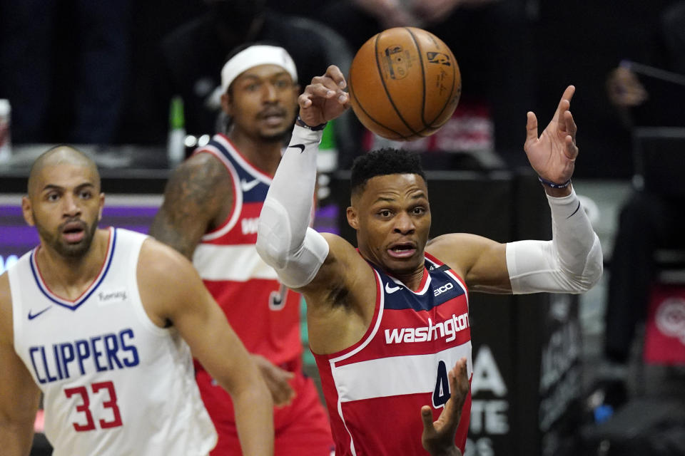 Washington Wizards guard Russell Westbrook, right, passes the ball as Los Angeles Clippers forward Nicolas Batum, left, and guard Wizards guard Bradley Beal watch during the first half of an NBA basketball game Tuesday, Feb. 23, 2021, in Los Angeles. (AP Photo/Mark J. Terrill)