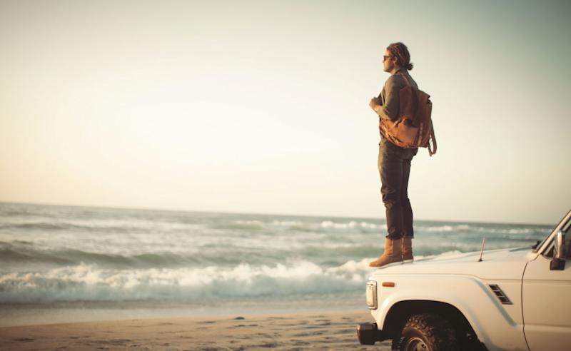 A man in Ugg boots stands on the hood of a truck on the beach.