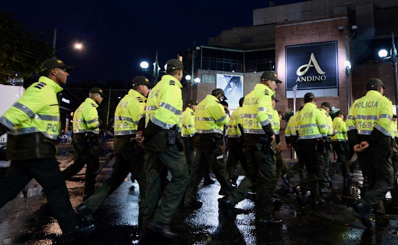 Colombian policemen respond to the bombing at a posh Bogota shopping centers which killed three people and injured nine