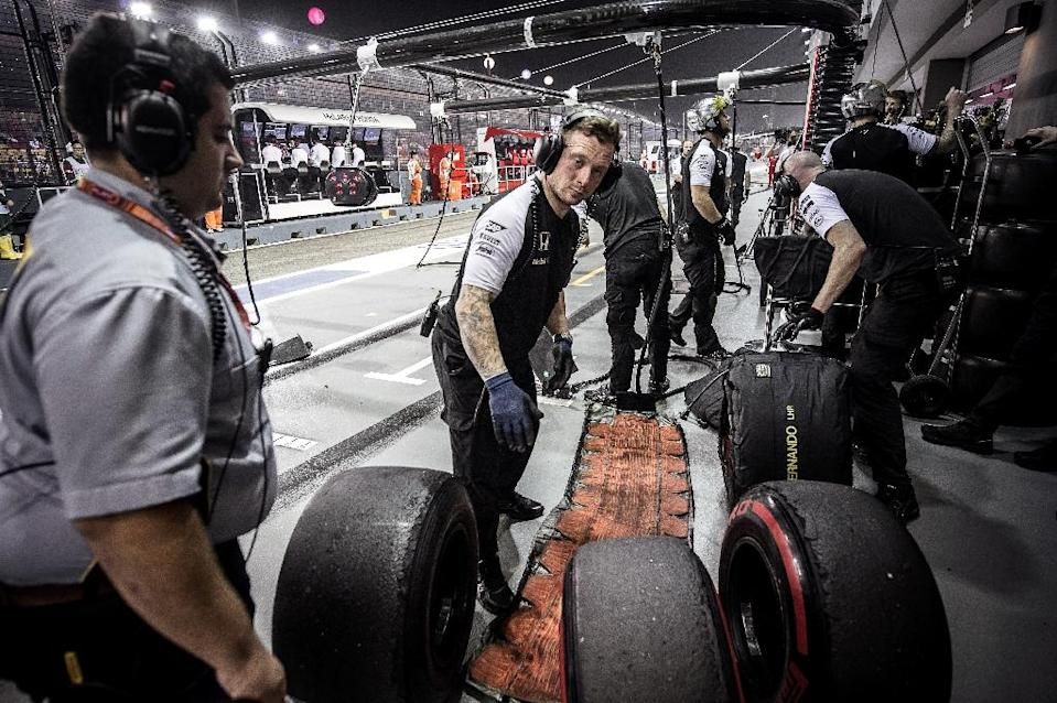 An official of Pirelli tyres (L) looks on as McLaren Honda's team members handle tyres during a practice session at the Singapore Grand Prix on September 18, 2015 (AFP Photo/Philippe Lopez)