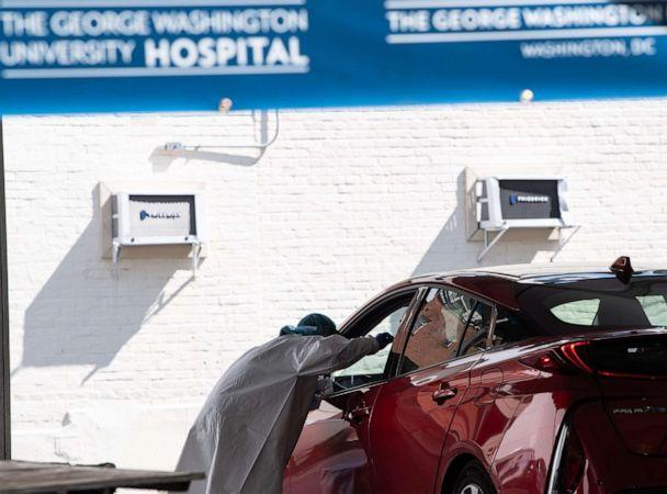 PHOTO: A nurse administers a COVID-19 test at a drive-through testing center at George Washington University in Washington, D.C., May 7, 2020. (Nicholas Kamm/AFP via Getty Images)