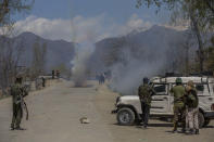 Indian policemen fire teargas shells at Kashmiri villagers as they throw stones and bricks at them during a protest near the site of a gunbattle in Pulwama, south of Srinagar, Indian controlled Kashmir, Friday, April 2, 2021. Anti-India protests and clashes have erupted between government forces and locals who thronged a village in disputed Kashmir following a gunbattle that killed three suspected militants. Police say the gunfight on Friday erupted shortly after scores of counterinsurgency police and soldiers launched an operation based on tip about presence of militants in a village in southern Pulwama district. (AP Photo/ Dar Yasin)