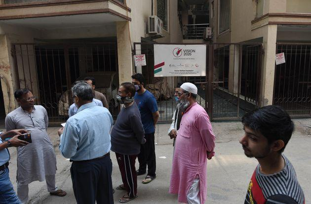People assembled outside the entrance gate to the Human Welfare NGO office where Delhi police conducted a raid this morning at Abul Fazal Enclave, in Jamia Nagar, on October 29, 2020 in New Delhi.