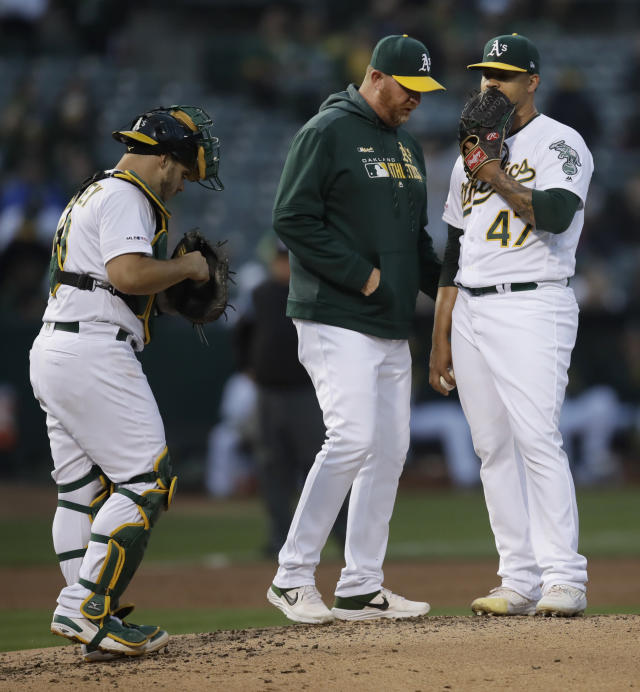 Oakland Athletics pitcher Frankie Montas, right, speaks with pitching coach Scott Emerson in the second inning of a baseball game against the Los Angeles Angels, Tuesday, May 28, 2019, in Oakland, Calif. (AP Photo/Ben Margot)