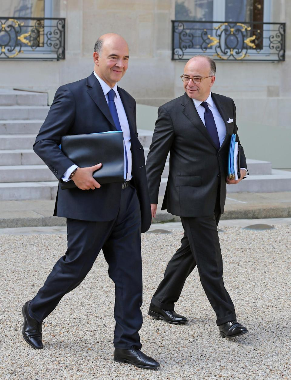 French finance minister Pierre Moscovici, left, and budget minister Bernard Cazeneuve, right, leave the Elysee Palace following the weekly cabinet meeting in Paris, Wednesday Sept. 25, 2013. The French government has declared the economic crisis over and is promising that its budget for next year will bring growth and jobs, but experts are criticizing the proposal from all sides and a true rebound looks way off.(AP Photo/Remy de la Mauviniere)