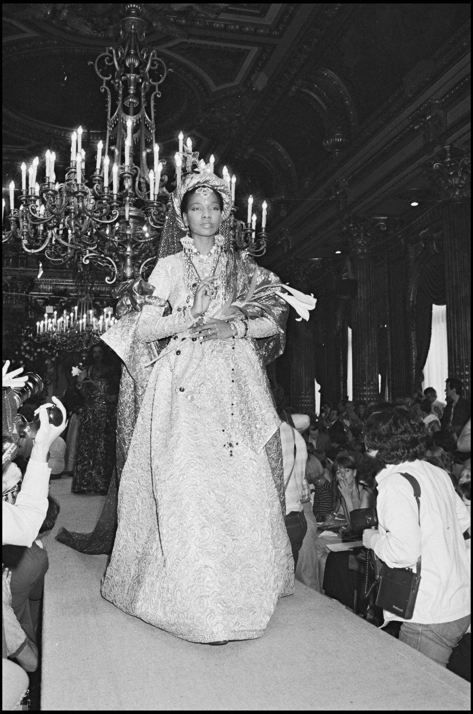 "<p>A muse of Yves Saint Laurent's in the 1970s and '80s, she was the <a href=""https://www.crfashionbook.com/fashion/g13987059/ysl-muses-throughout-history/"" rel=""nofollow noopener"" target=""_blank"" data-ylk=""slk:first Black model he booked in his haute couture shows"" class=""link rapid-noclick-resp"">first Black model he booked in his haute couture shows</a>. Throughout her modeling career, she almost exclusively worked with Saint Laurent.</p>"