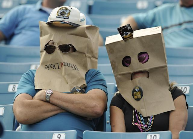 Disappointed Jacksonville Jaguars fans wear bags on their heads as they watch their team lose to the San Diego Chargers 24-6 in an NFL football game in Jacksonville, Fla., Sunday, Oct. 20, 2013. (AP Photo/Stephen Morton)