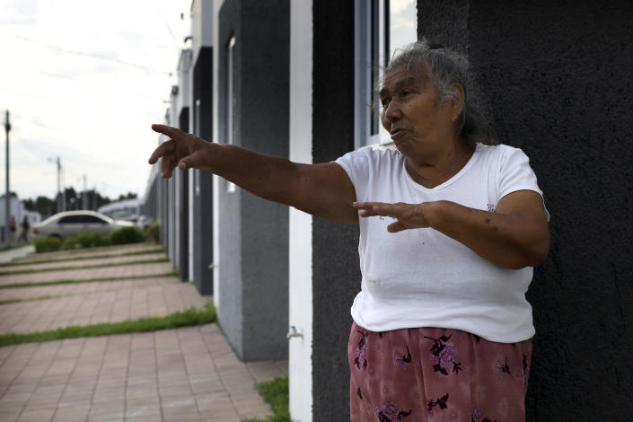 """Victoria Crisostoma, a survivor of the October 2002 landslide that devastated her community Los Angelitos, speaks during an interview from the doorstep of her new government donated home, in the private residential development Ciudad Marsella, El Salvador, Tuesday, July 27, 2021. The 73-year-old grandmother said, """"We are not allowed to cook with wood and we have to pay for gas. I cannot afford it. We are not allowed to grind corn so I cannot make my own tortillas and I have to buy them. I have no income."""" (AP Photo/Salvador Melendez)"""