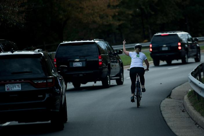 <p>OCT. 28, 2017 – A woman on a bike gestures with her middle finger as a motorcade with President Donald Trump departs Trump National Golf Course October 28, 2017 in Sterling, Virginia. She was fired from her job the following week. (Photo: Brendan Smialowski/AFP/Getty Images) </p>