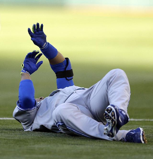 Toronto Blue Jays' Edwin Encarnacion rolls on the field after tripping while running to first base in the first inning of a baseball game against the Oakland Athletics on Saturday, July 5, 2014, in Oakland, Calif. Encarnacion left the game with an injury.(AP Photo/Ben Margot)