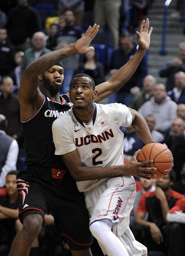 Connecticut's DeAndre Daniels (2) drives past Cincinnati's Titus Rubles (2) during the first half of an NCAA college basketball game in Hartford, Conn., Sunday, March 1, 2014. (AP Photo/Fred Beckham)