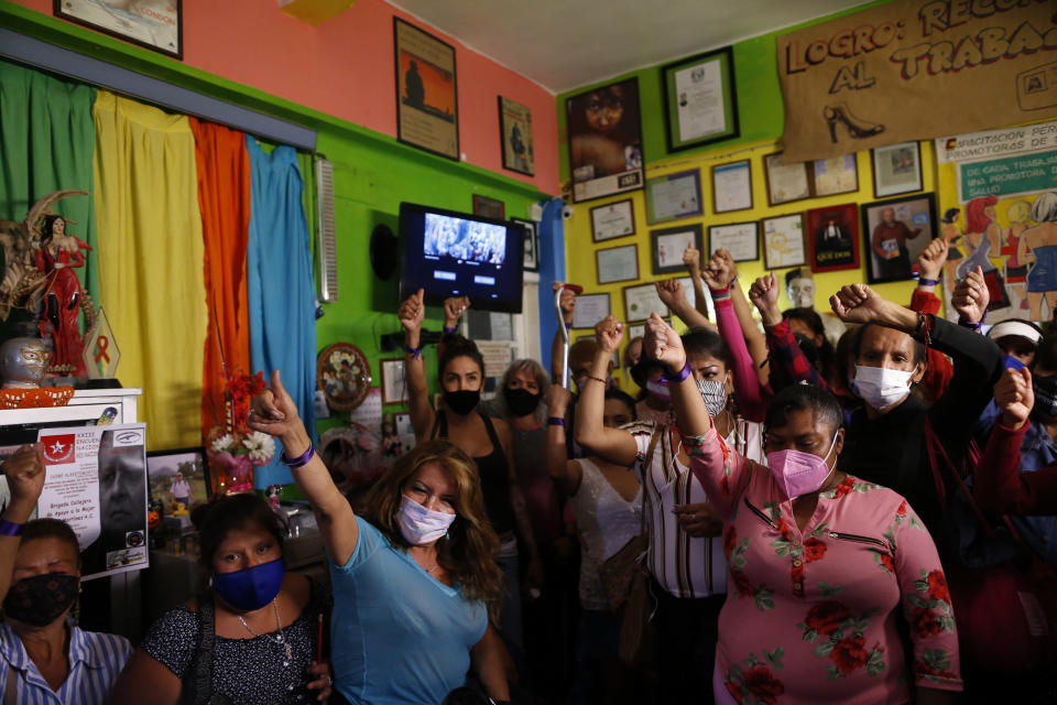 """Sex workers raise their fists in solidarity after telling stories about their personal experiences, during a nationwide virtual event to advocate against human trafficking and in favor of rights and recognition for sex workers, ahead of International Women's Day, at the offices the activist group Brigada Callejera or """"The Street Brigade"""", in Mexico City, Saturday, March 6, 2021. (AP Photo/Rebecca Blackwell)"""