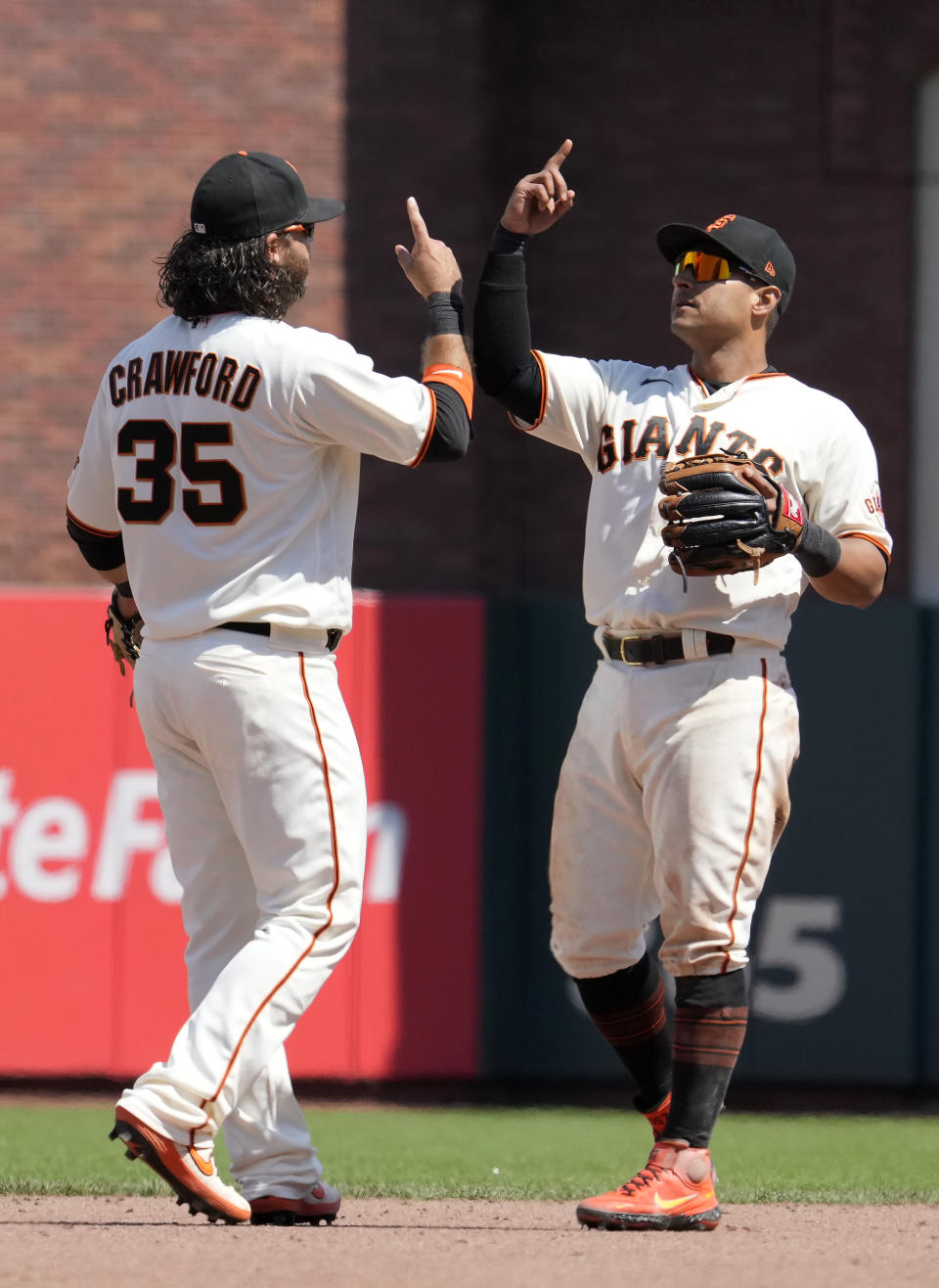 San Francisco Giants shortstop Brandon Crawford (35) and second baseman Donovan Solano celebrate the team's 5-0 victory over the Los Angeles Dodgers in a baseball game Thursday, July 29, 2021, in San Francisco. (AP Photo/Tony Avelar)